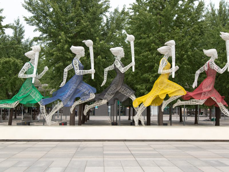 Sculpture of running figures in the colours of the Olympic rings
