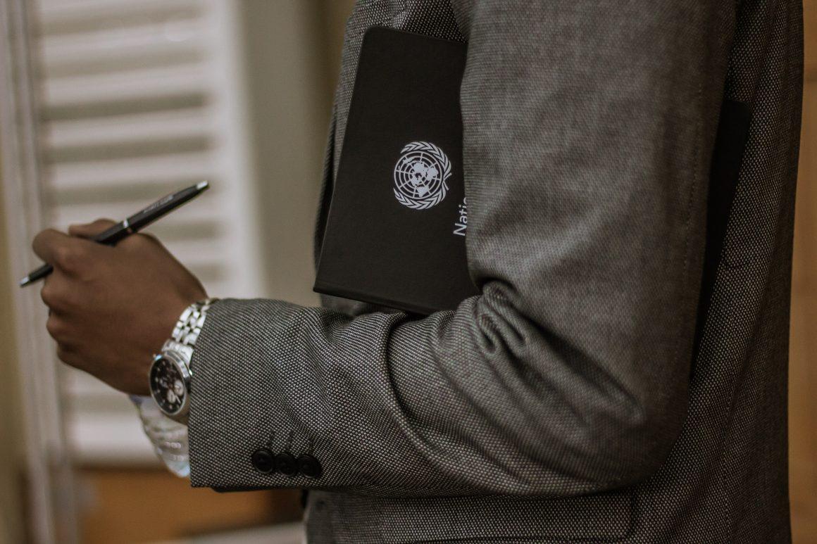 Man holding a UN folder under his arm